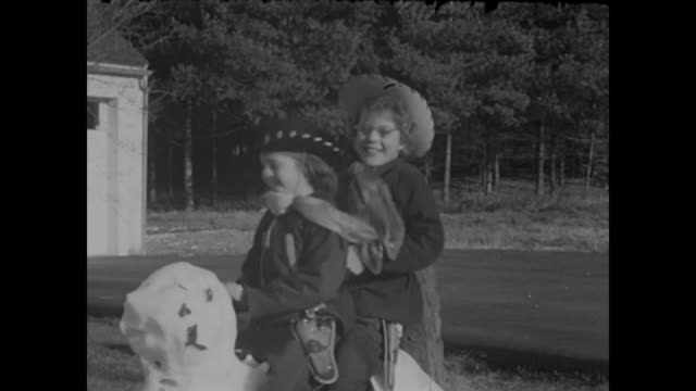 1950s young girls dressed as cowboys play with horse made of snow - home movie - small town stock videos & royalty-free footage