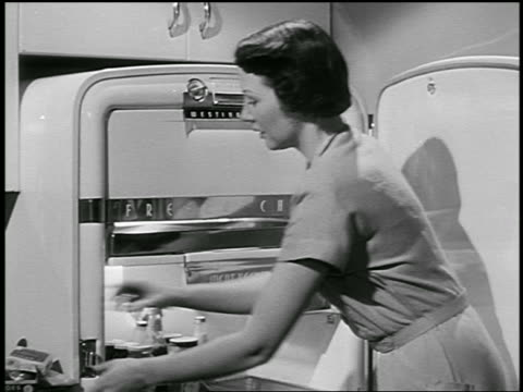 B/W 1950s zoom out housewife loading up freezer + refrigerator with groceries / industrial