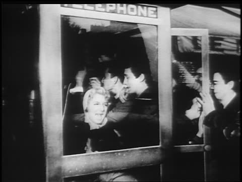 B/W 1950s/60s crowd of teens stuffed into telephone booth / newsreel