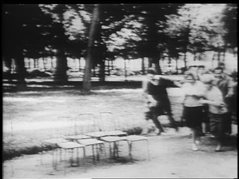 B/W 1950s/60s PAN from man blowing whistle to teens crowding onto chairs outdoors / newsreel