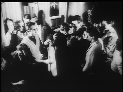 B/W 1950s/60s high angle crowd of teens dancing in crowded room / newsreel