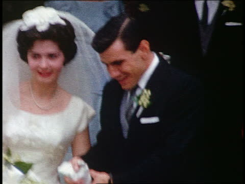 1950s/60s home movie bride + groom exiting church after wedding / rice being thrown - home movie stock videos & royalty-free footage