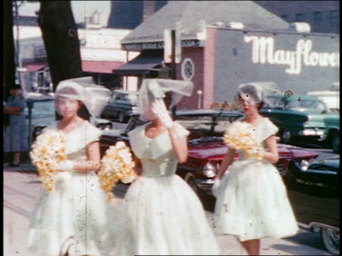 vídeos de stock, filmes e b-roll de 1950s/60s home movie pan bridesmaids carrying bouquets walking on sidewalk - bridesmaid