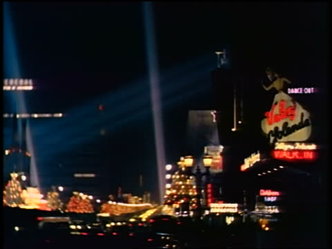 1950s/60s long shot beams of klieg lights arcing across sky above neon signs + lights of city at night