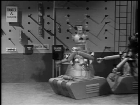 B/W 1950s/60s out of control robot spinning around + running into second robot