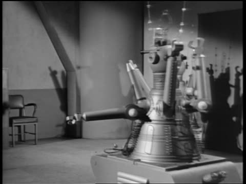 B/W 1950s/60s robot rolling into room + stopping next to second robot