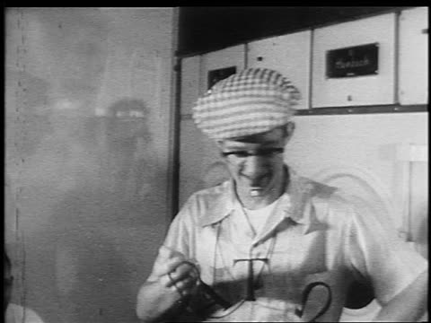 B/W 1950s/60s teen boy in eyeglasses + hat with whistle in mouth holding stopwatch turns