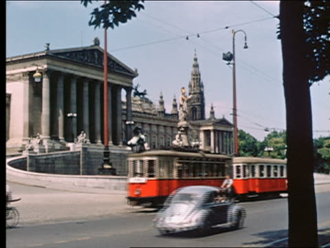 1950s/60s trolley + traffic pass in front of ornate parliament building + statues / vienna, austria - autorität stock-videos und b-roll-filmmaterial