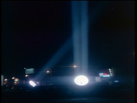 vídeos de stock e filmes b-roll de 1950s/60s two large klieg lights rotating with beams shining into night sky - holofote
