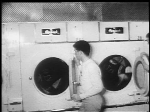 b/w 1950s/60s two teen boys in fraternity sweaters + helmets spinning in clothes dryers - waschsalon stock-videos und b-roll-filmmaterial