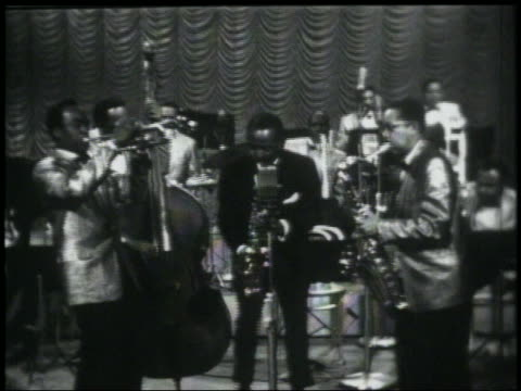 B/W 1950s/60s zoom in Louis Jordan playing saxophone on stage with band / he starts singing