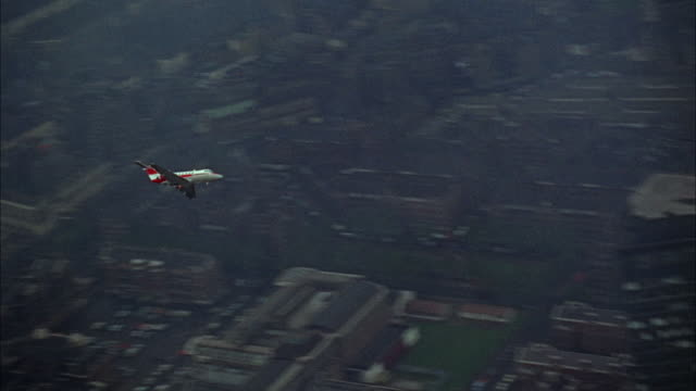 1960s aerial ws pan airplane flying over city / london, uk - air to air shot stock videos and b-roll footage