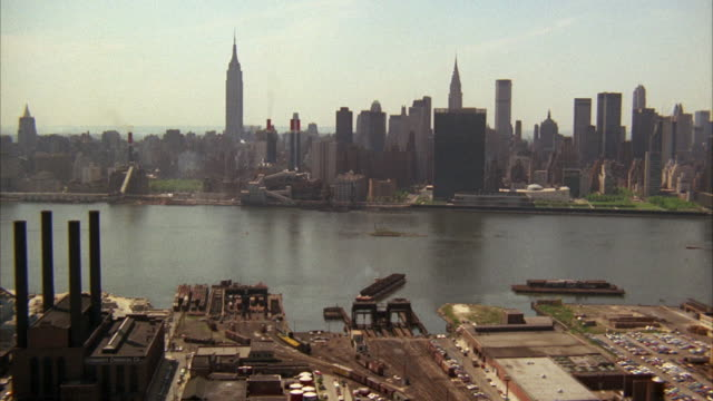 1960s aerial ws east river with manhattan skyline / new york city, usa - anno 1968 video stock e b–roll