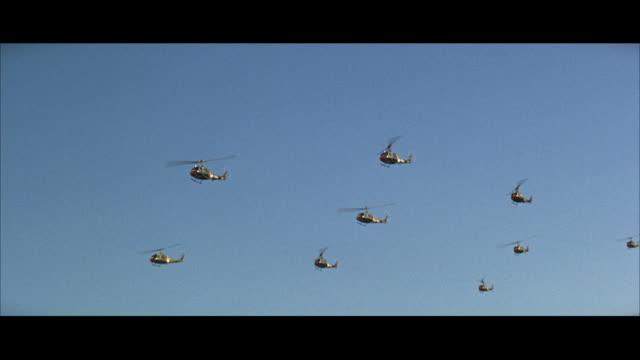 vídeos de stock, filmes e b-roll de 1960s aerial ws group of military helicopters in flight - helicóptero