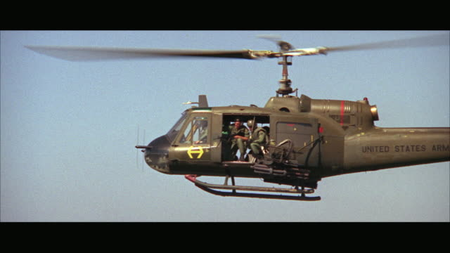 1960s MS AERIAL Military helicopter in flight with soldiers inside