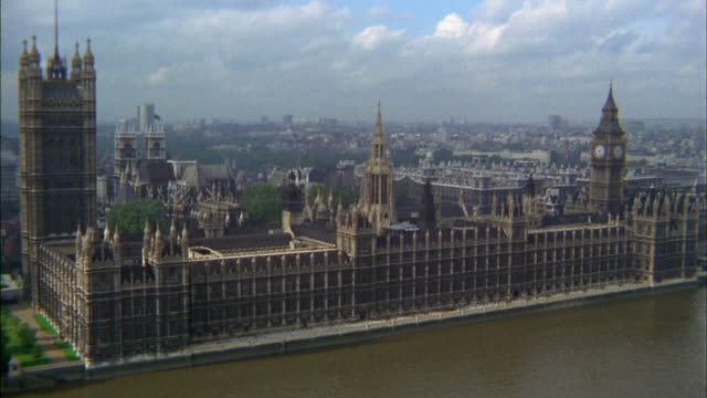 1960s aerial point of view Houses of Parliament and Thames river / zoom in Big Ben clock tower / London
