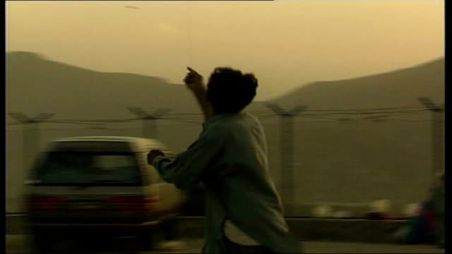 1960s and 1970s background; ext young boy flying kite at sunset barbed wire fence with setting sun in background - afghanistan stock videos & royalty-free footage
