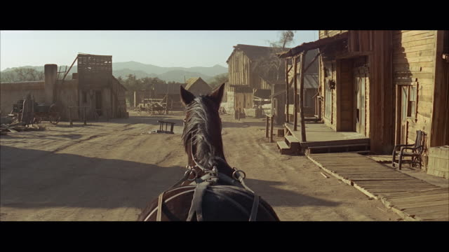 vidéos et rushes de 1960s ws pov back of harnessed horse in old west town - ouest américain