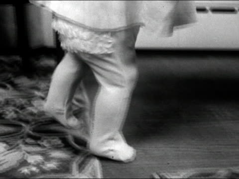 1960s black and white close up legs of baby in footie pants taking first steps / audio - first occurrence stock videos & royalty-free footage
