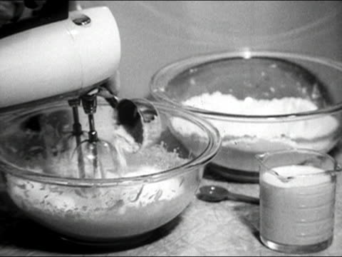vídeos de stock, filmes e b-roll de 1960s black and white close up woman adding flour to mixing bowl as she uses electric mixer / audio - tigela louça