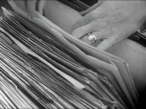 1960s black and white close up woman rifling through files - filing cabinet stock videos & royalty-free footage