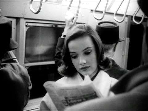 1960s Black and white Close up young woman reading newspaper on subway train / AUDIO