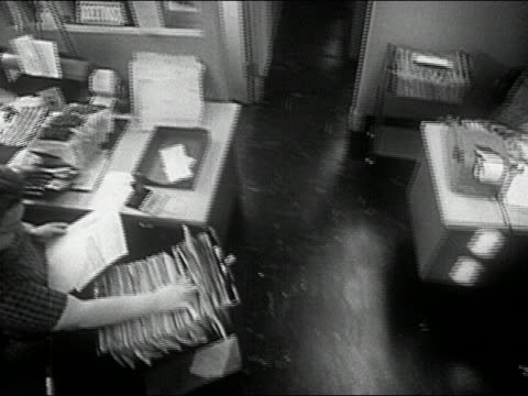 1960s black and white high angle crane shot overhead shot of women working in an office