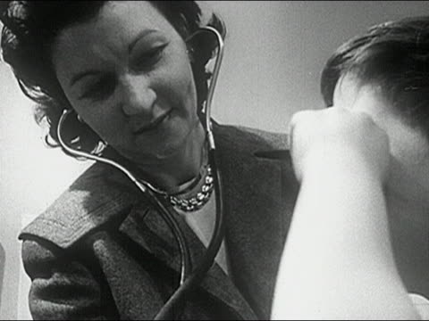 1960s black and white low angle close up female doctor examining boy with stethoscope / boy rubbing eyes