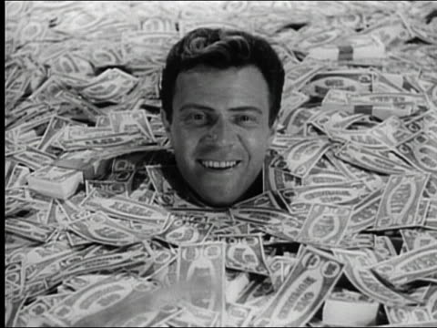 1960s black and white man buried up to his head in money smiling and looking up as bills fall down around him