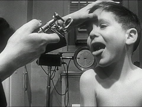 1960s black and white medium shot doctor examining boy's throat with stethoscope / boy sticking out tongue - boy medical exam stock videos and b-roll footage
