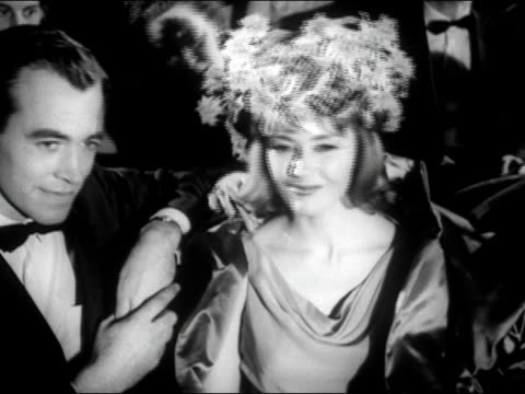 1960s black and white medium shot man in tuxedo and woman wearing elaborate hat with flowers watching theatre performance / woman behind them asking woman to remove hat / audio - dinner jacket stock videos & royalty-free footage