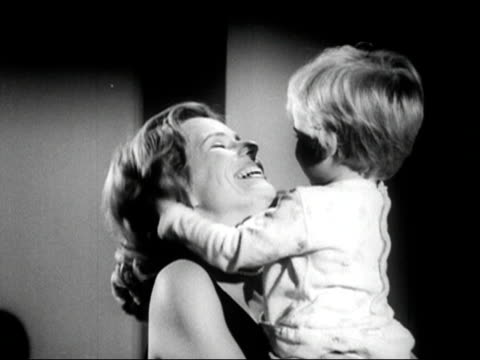 1960s Black and white Medium shot mother holding toddler son as he plays with her hair / boy messing up his own hair / AUDIO