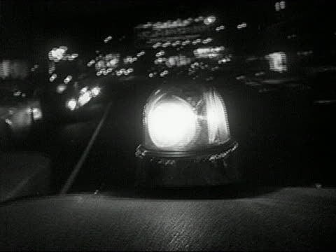 1960s black and white medium shot point of view flashing light on ambulance driving on city street at night - emergency light stock videos & royalty-free footage