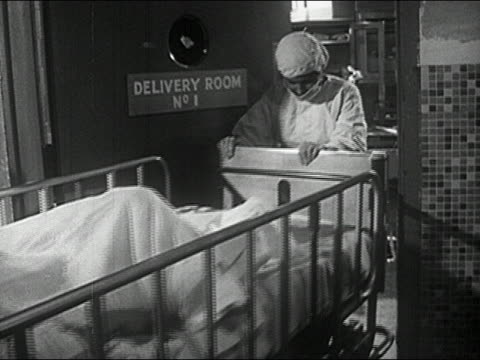 1960s black and white medium shot pregnant woman on stretcher being wheeled into delivery room by doctor