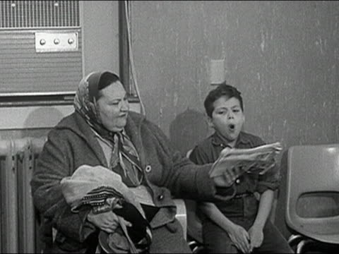 1960s black and white medium shot woman putting newspaper in front of mouth of coughing boy / boy covering mouth with hand