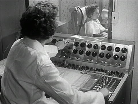 1960s black and white medium shot woman sitting at EEG control panel turning knobs / treating women in next room