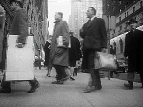 1960s black and white slow motion low angle medium shot pedestrians walking on busy city sidewalk