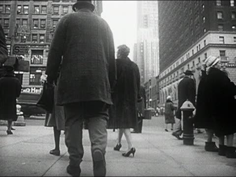 1960s black and white slow motion low angle medium shot pedestrians walking on busy city sidewalk - 毛皮のコート点の映像素材/bロール