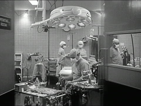 1960s black and white wide shot dolly shot operating room doors opening / doctors preparing for surgery