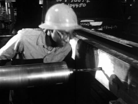 b/w 1960s black man in hard hat + safety glasses operating large drill into metal / documentary - drill stock videos & royalty-free footage