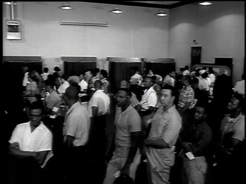 1960s ws black men and women standing in line at polling station / united states - 投票点の映像素材/bロール