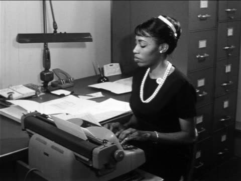 B/W 1960s Black woman typing on typewriter at desk in office / documentary