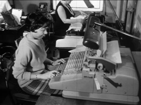 B/W 1960s Black woman typing on typewriter at desk in office with other workers / documentary
