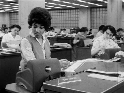 b/w 1960s black woman with adding machine writing on paper on desk in office full of workers - dokument stock-videos und b-roll-filmmaterial