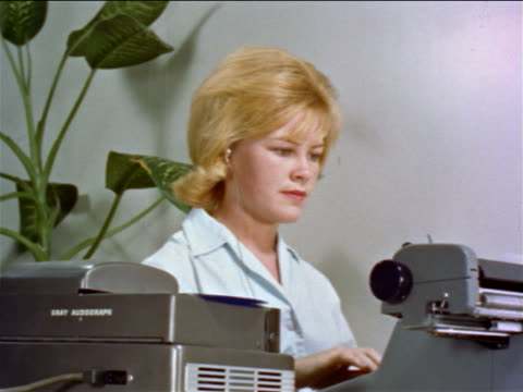 1960s blonde woman typing on typewriter while listening to dictaphone in office / educational - secretary stock videos & royalty-free footage