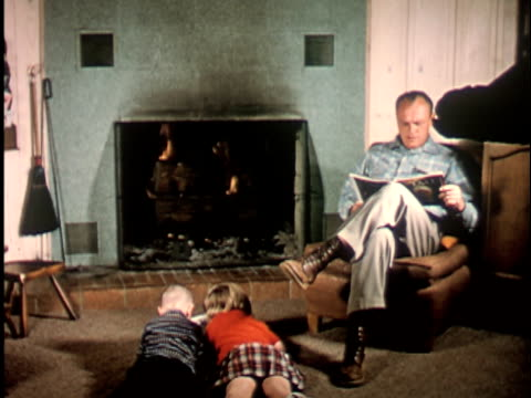 ws 1960s boy and girl lying in front of fireplace, father sitting in chair reading magazine, california / usa - zeitschrift stock-videos und b-roll-filmmaterial