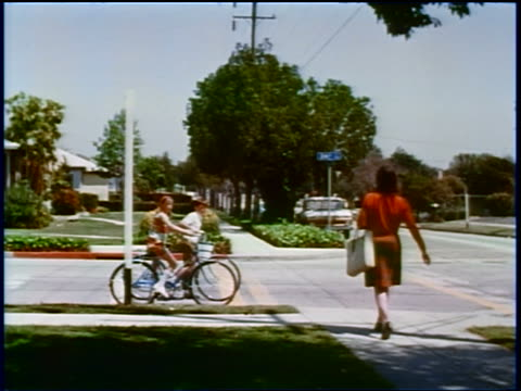 1960s PAN boy + girl riding bicycles stop to let woman cross street + van drive by at intersection