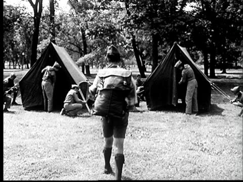 """1960s WS Boy scout walking away from camera toward camp where other scouts are pitching tents/ St. Louis, Missouri"""