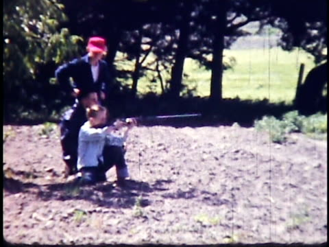 stockvideo's en b-roll-footage met 1960s ws boys and male adult practicing with bb gun or 22 caliber riffle / california, usa - geweer