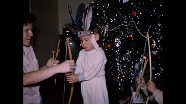 vídeos de stock e filmes b-roll de 1960s boys wearing indian headdresses open christmas presents - home movie - cultura tribal da américa do norte